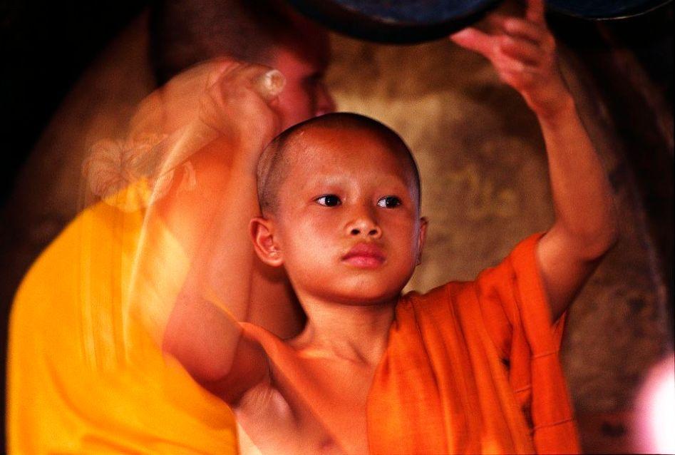 A novice monk bang the Xieng Thong Pagoda drum in Luang Prabang.