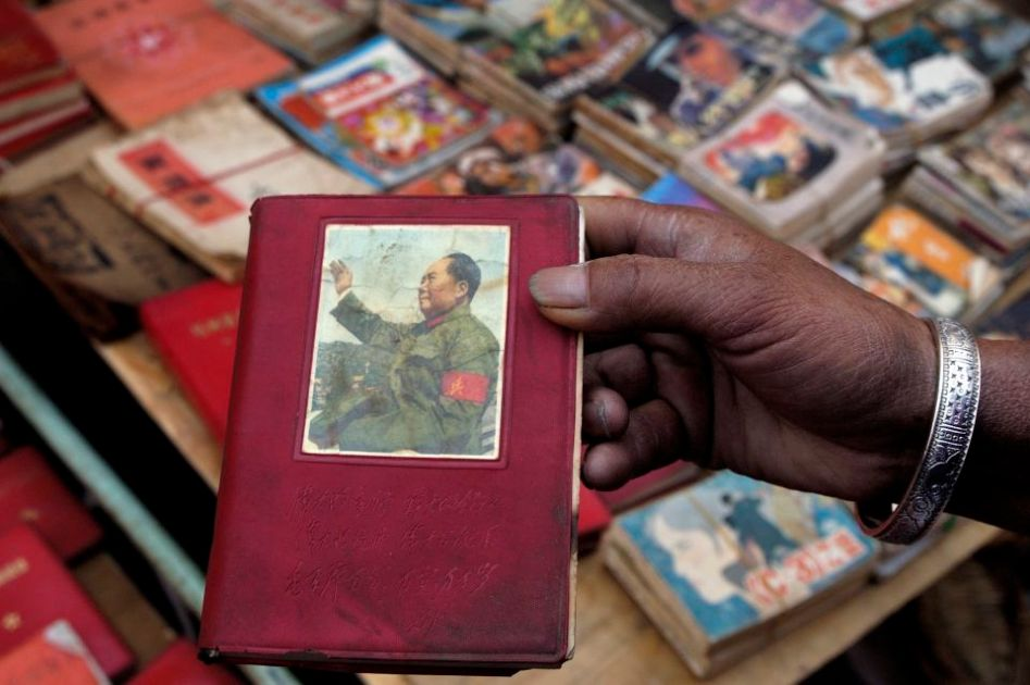 At a street market in Yunnan province, China. A woman display an old copy of Mao's Red book.