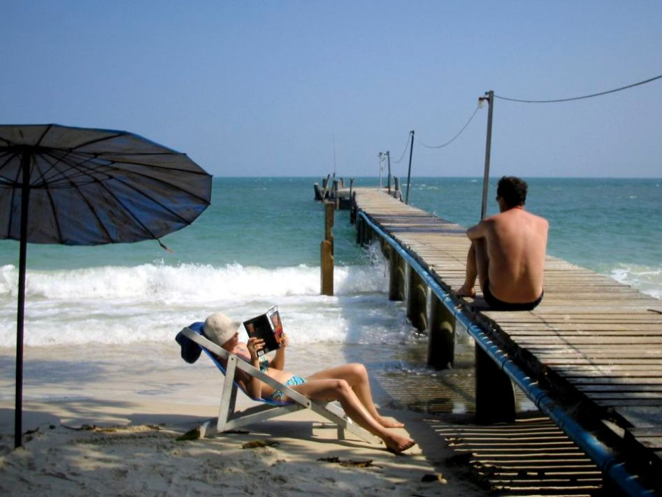 A couple of tourist rest on the egde of the sea at a beach in Thailand.