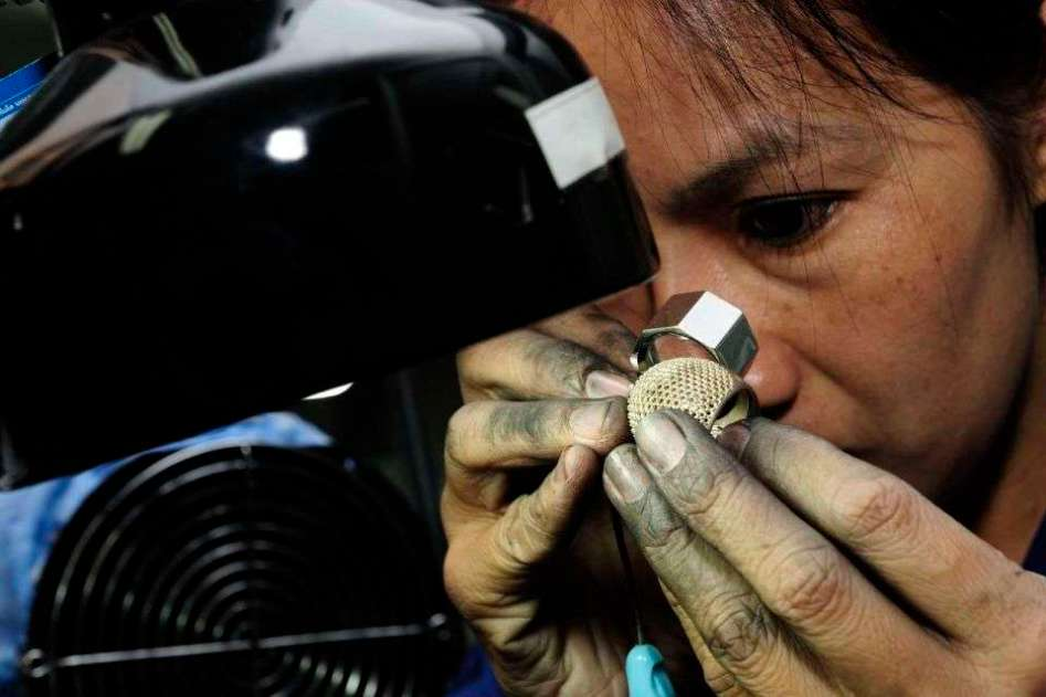 A woman working on a gold ring at a jewelry house in Bangkok.
