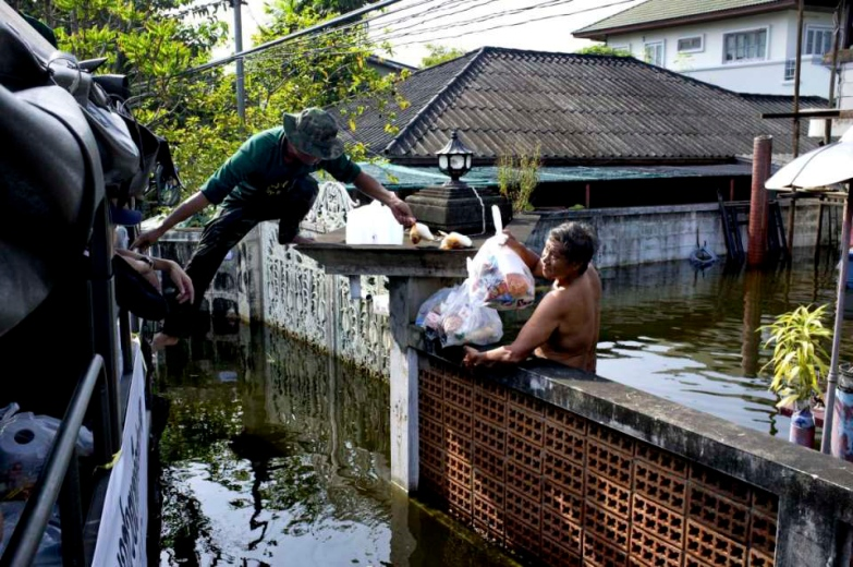 Food distribution by the Thai Army to the victims of the floods. People who have stayed in their submerged houses are getting little access to food as they have to reach the distributions points. A man reach over the wall of his house to collect the food bags.
