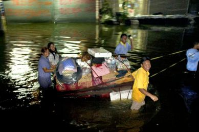 A family trail their belonging in the night, on a makeshift raft. They are travelling along a major road of this area about 25 km from Bangkok