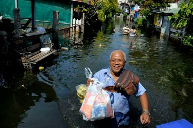 Fllooded neighborhood of Bang Phlat and Taling Chan on the western side of the Chaopraya river. Distribution of Food supplies and water from an Thai army truck. A man is all smile after getting his share of supllies.