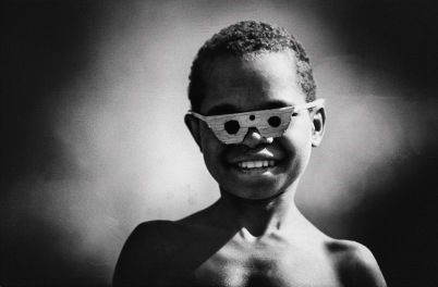 Irian Jaya. 1982. A young boy from the Dani tribe wearing wooden frames.