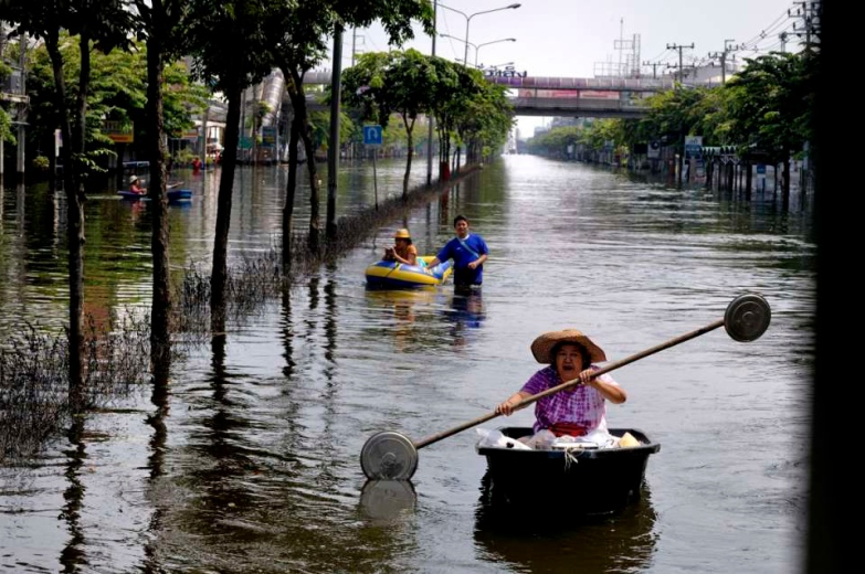 Fllooded neighborhood of Bang Phlat and Taling Chan on the western side of the Chaopraya river. Distribution of Food supplies and water from an Thai army truck. Paddling you way on a main thouroughfare of Taling Chan in Western Bangkok.