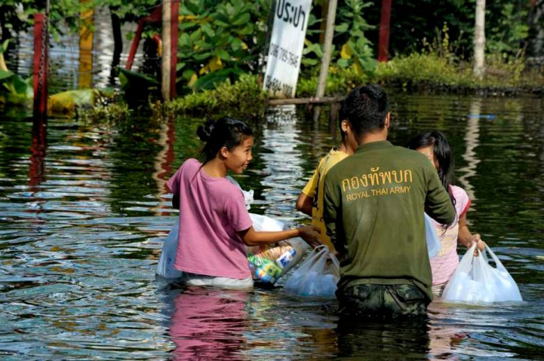 Fllooded neighborhood of Bang Phlat and Taling Chan on the western side of the Chaopraya river. Distribution of Food supplies and water from an Thai army truck. A thai soldiers hands bags of foods to residents in Taling Chan and get a smile in return.