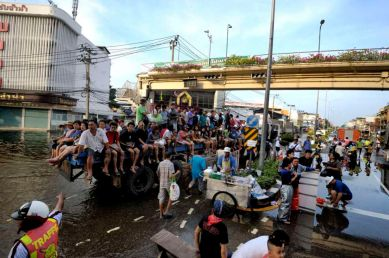 Fllooded neighborhood of Bang Phlat and Taling Chan on the western side of the Chaopraya river. Distribution of Food supplies and water from an Thai army truck. The new adhoc transport sysm in the flood area using a flatbed trailer.
