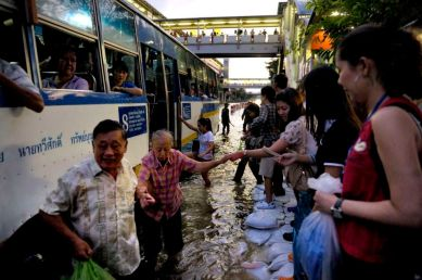In the area of Payonyothin and Latprao roads, commuting in water clogs major street is time consuming. Althought the underground and the elevated trains sysms are still working, once you get at the stations, the hardship starts. An elderly woman getting a hand at the bus station.