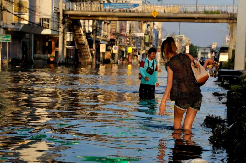 A young woman gors back to her house in flooded Thonburi side of the city after a night out.