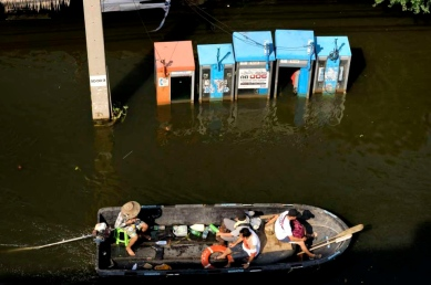 On the north side of Bangkok, along the main highway in Rangsit. People in boats on the highway.