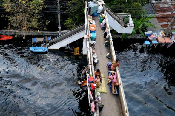 In Rangsit area, this family who's house is under 10 feet of water in the Muang Ake village/golf course, has decide to stay on a foot path above the flooded street and just below the expressay north of Bangkok