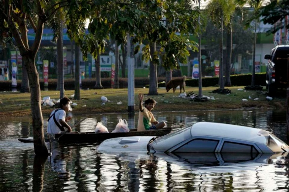 Pathum Thani is an industrial area North of Bangkok and It's main road is flooded. It's bordered on its South by the Rangsit canal along which a 20+ km sandbag wall was build to stop the water going to Bangkok. Boating on the highway.