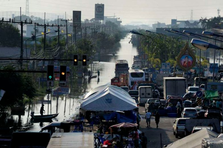 Pathum Thani is an industrial area North of Bangkok and It's main road is flooded. It's bordered on its South by the Rangsit canal along which a 20+ km sandbag wall was build to stop the water going to Bangkok. A dry spot provide a base for food distribution.