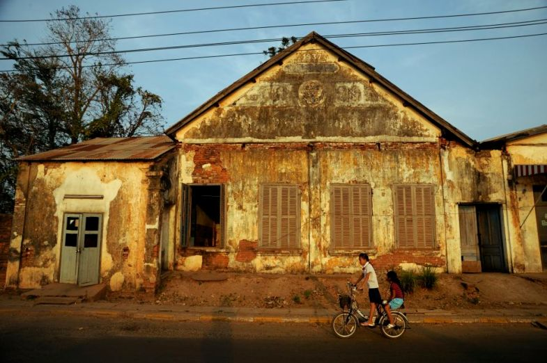 Chidren riding a bycle past a decrepit old colonial building in the city of Savannakhet.